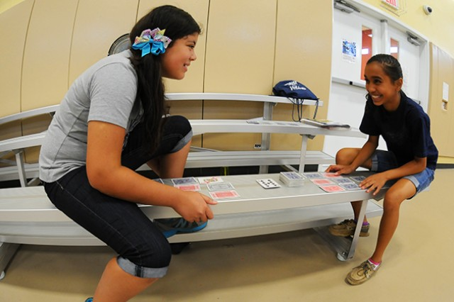 Cristina Arias and Nykia Hanner play a card game at the Fort Rucker Youth Center July 27 during the center's summer camp. The Back to School Bash takes place Aug. 17.