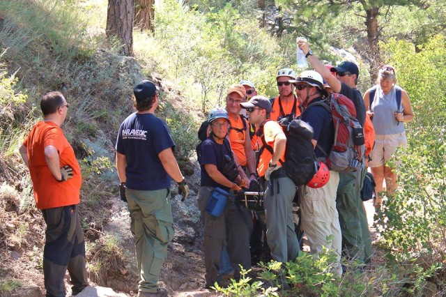 Capt. Ronald Bailey, Headquarters and Headquartes Battery, 100th Missile Defense Brigade (Ground-based) Midcourse Defense), wearing the orange hat and shirt, holds the litter as the rescue crews descend the trail after responding to a hiker who had fallen and broken her wrist July 31 in Lory State Park near Fort Collins, Colo.