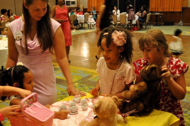 """A full house attended the Mommy and Me Tea, July 27, in the Community Activity Center. Mothers, daughters and their dolls were able to get all dressed up and spend some quality time together, participating in a """"proper"""" English-style tea party."""