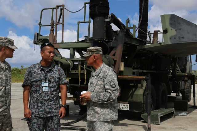 U.S. Army Capt. Jason Windham, commander of Charlie Battery, 1st Battalion, 1st Air Defense Artillery, discusses the value of training with Capt. Kiyotaka Higuchi, Chief, Foreign Liaison, Headquarters Southwest Composite Air Division at Kadena Air Base in Okinawa, Japan, July 17, 2013.  (U.S. Army photo by Charles Steitz/Released)