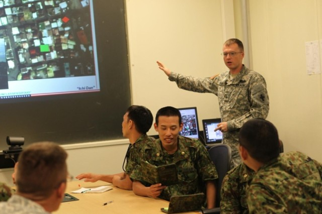 U.S. Army Sgt. Kyle R. Paine instructs the 10th Regional Support Group Intelligence Section and soldiers from the 15th Brigade, Japanese Ground Self Defense Force G2 section on July 24th at Torii Station during the first intelligence bilateral exchange held between the two units. During the training they went over basic soldiering skills as well as intelligence analytical techniques.