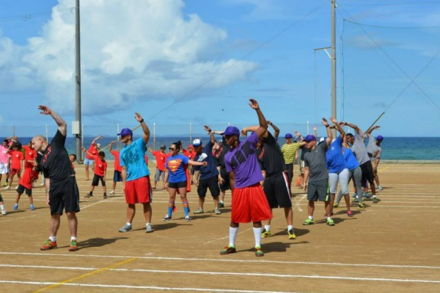 """22 Soldiers and Family Members from the 10th Regional Support Group do """"radio stretches"""" at the Annual Sobe Ward Sports Day on July 28 in Yomitan.  For the last seven years the Army has participated in this annual event to foster positive relationships and to enjoy a day of healthy competition with the citizens of Sobe Ward."""
