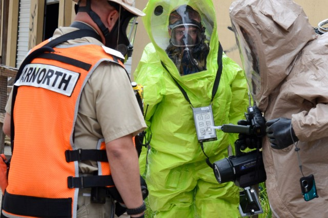 "MUSCATATUCK URBAN TRAINING CENTER, Ind. "" Two Soldiers from the 52nd Weapons of Mass Destruction-Civil Support Team, Ohio National Guard, discuss their sampling results with a U.S. Army North (Fifth Army) observer controller July 31 during a simulated Chemical, Biological, Radiological, Nuclear incident scenario. The scenario was part of the Vibrant Response 13-2 training exercise at Muscatatuck Unit Training Center.  VR 13-2 is a major incident exercise conducted by U.S. Northern Command and led by U.S. Army North (Fifth Army). The observer controller asked questions of the Soldiers concerning testing results and what additional tests or samples if any, would be necessary."