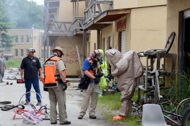 "MUSCATATUCK URBAN TRAINING CENTER, Ind. "" Two Soldiers from the 52nd Weapons of Mass Destruction-Civil Support Team, Ohio National Guard, collect samples to detect Chemical, Radiological, Nuclear incident scenario during the Vibrant Response 13-2 training exercise July 31 at Muscatatuck Urban Training Center, Muscatatuck, Ind.  VR 13-2 is a major incident exercise conducted by U.S. Northern Command and led by U.S. Army North (Fifth Army). The CST team is responsible for detecting and identifying chemical, biological, radiological and nuclear agents in the area prior to first responders entering the incident site."
