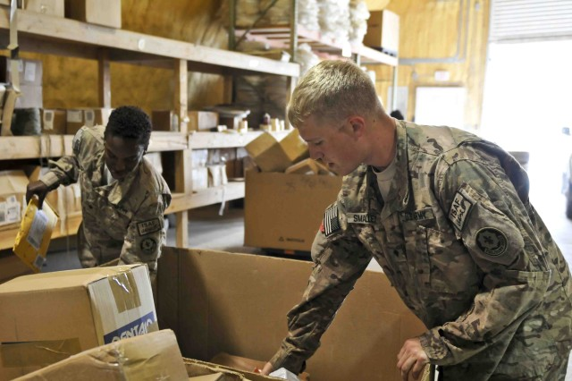 U.S. Army Spc. Terry Smalley (right) and Spc. Dychambra West, both with Headquarters and Headquarters Troop, Combined Task Force Dragoon, sort and separate their unit's mail Aug. 3, 2013 at Kandahar Airfield, Afghanistan. Smalley and West work with United States Postal Service employees to bring parcels and letter mail to the members of the task force. (U.S. Army Photo by Spc. Joshua Edwards)