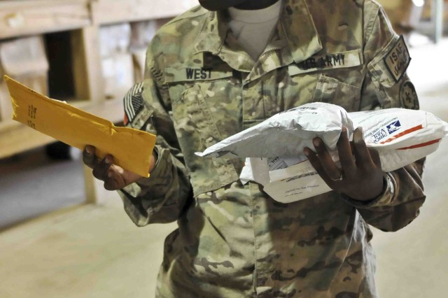 U.S. Army Spc. Dychambra West with Headquarters and Headquarters Troop, Combined Task Force Dragoon, sorts and separates her unit's mail Aug. 3, 2013 at Kandahar Airfield, Afghanistan. West and other soldiers work with United States Postal Service employees to bring parcels and letter mail to the members of the task force. (U.S. Army Photo by Spc. Joshua Edwards)