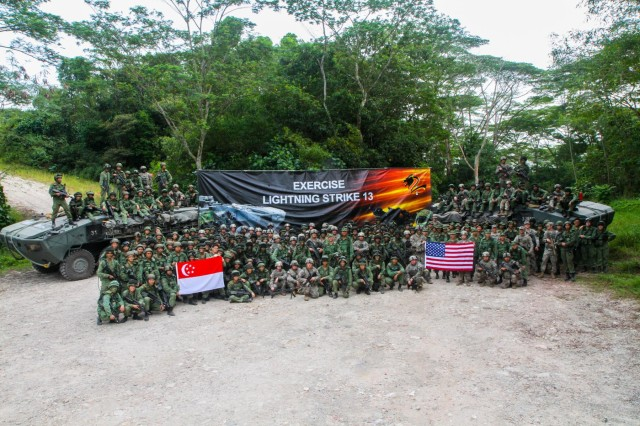 Members of 2nd Battalion, Singapore Infantry Regiment, and U.S. Army Soldiers with 4th Battalion, 23rd Infantry Regiment, 2nd Brigade, 2nd Infantry Division, stand together after concluding a 4-day training mission in Singapore July 25, 2013. The training mission was part of Exercise Lightning Strike, a 12-day event sponsored by U.S. Army Pacific.