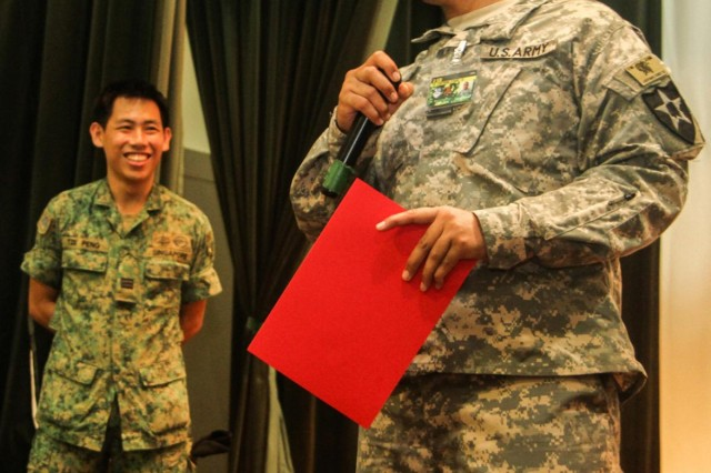 U.S. Army Staff Sgt. Iakopo Tei, a squad leader with 4th Battalion, 23rd Infantry Regiment, 2nd Brigade, 2nd Infantry Division, thanks Singaporean soldiers with 2nd Battalion, Singapore Infantry Regiment, for their hospitality during a ceremony July 26, 2013. The ceremony celebrated the conclusion of Exercise Lightning Strike, a U.S. Army Pacific sponsored event that partnered U.S. and Singaporean Soldiers.