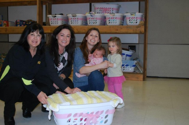 Support Americas Armed Forces volunteer Vicky Mohler and Wendi Hinton pass out a girl baby bundle to Katherine Allen for her newborn baby girl during a monthly meeting of the Pacemaker Pregnancy Support Group, a support group for new and expecting mothers of the 864th Engineer Battalion.  The baby bundles, generously donated by SAAF, consist of the basics for taking care of a newborn baby-to include baby wipes, formula, bottles, toiletries, and hand knit quilts and hats made by volunteers from Quilts from the Hearts.