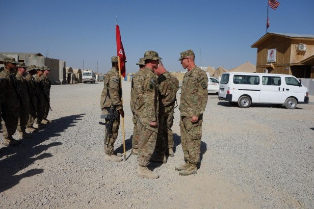 Lt. Col. Hibner and Command Sgt. Maj. Stanley place combat patches on the Forward Support Company's command team, July 4, 2013. The Forward Support Company runs logistical missions throughout southern Afghanistan.