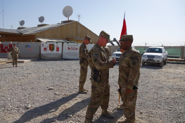 Lt. Col. Hibner and Command Sgt. Maj. Stanley place combat patches on the Headquarters and Headquarters Company's command team, July 4, 2013. The Headquarters and Headquarters Company ensures the proper functioning of the battalion staff.