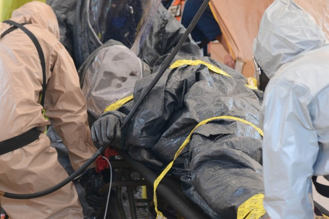 "Lt. Col. Jeffrey Suver (center), commander of the 52nd Weapons of Mass Destruction-Civil Support Team, Ohio National Guard, is tested for residue from chemical agents, Aug. 1, 2013, after being doused in water by his Soldiers in a ""man-down"" scenario in a contaminated area scenario during the Vibrant Response 13-2 training exercise at the Muscatatuck Urban Training Center, Ind.  Vibrant Response 13-2 is a major incident exercise conducted by U.S. Northern Command and led by U.S. Army North (Fifth Army), which is based out of Fort Sam Houston, Texas. During the scenario, the commander notionally ""fell"" while clearing a building that was suspected of having some chemical agents inside and was required to go through the decontamination station as a non-ambulatory patient."