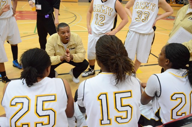 "Lt. Col. William ""Nate"" Johnson, chief of current operations, 94th Army Air and Missile Defense Command, and 2013 All Army Women Basketball team head coach, goes over defensive strategies with members of the All Army Women Basketball team during a time out."