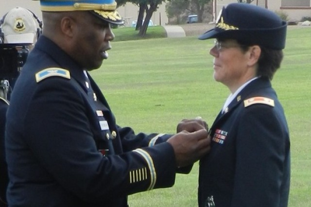 Lt. Col. Dionne Wilson receives the Meritorious Service Medal from Col. Frederick Washington, Training and Doctrine Command capability manager for Biometrics and Forensics, during the installation retirement ceremony July 26 on Brown Parade Field. Wilson was among five Soldiers honored during this quarter's ceremony.