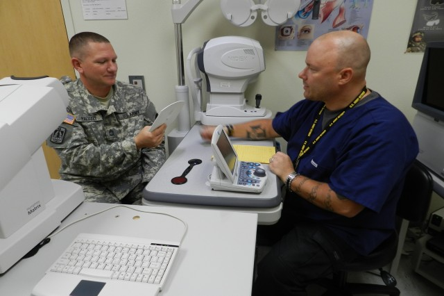 From left, Master Sgt. Christopher Paluzzi, senior signal operations noncommissioned officer in charge, Information Systems Engineering Command, receives his pre-testing part of the eye exam from Randy Maurer, Optometry Clinic technician. The Optometry Clinic is located inside Raymond W. Bliss Army Health Center.