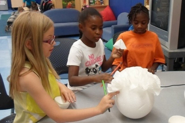 "Eva Williams, Thalia Frasier and Madison Fields-Herring use a styrofoam ball and coffee filters to create a hanging decoration for the 4th of July. The craft related to this Seifert School Age Center's summer program theme, an ""Old-fashioned Summer."""
