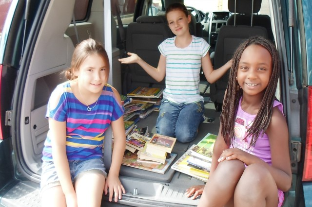 From left, Crystal Cooper, Chantal Lee and Nyla Johnson participate in a bookmobile activity during Seifert School Age Center's summer program. Not only did children participate in recreational activities, but they also were encouraged to read.