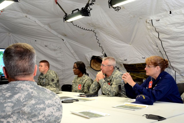 Coast Guard Rear Adm. June E. Ryan, military advisor to the Secretary U.S. Department of Homeland Security, receives a briefing on how the scenarios are planned during the U.S. Army North led exercise Vibrant Response 13-2, Camp Atterbury, Ind., Aug. 3, 2013.  Ryan visited Camp Atterbury and Muscatatuck Urban Training Center to better understand the level of extensive training and opportunities available through the use of facilities during exercises such as Vibrant Response 13-2.