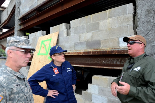 Coast Guard Rear Adm. June E. Ryan, military advisor to the Secretary U.S. Department of Homeland Security, receives a brief from a civilian contractor concerning the collapsed parking garage scenario at the Muscatatuck Urban Training Center, near Muscatatuck, Ind., Aug. 3, 2013. Ryan visited Camp Atterbury along with MUTC to better understand the level of extensive training and opportunities available through the use of the facilities during exercises such as U.S. Army North's Vibrant Response 13-2.