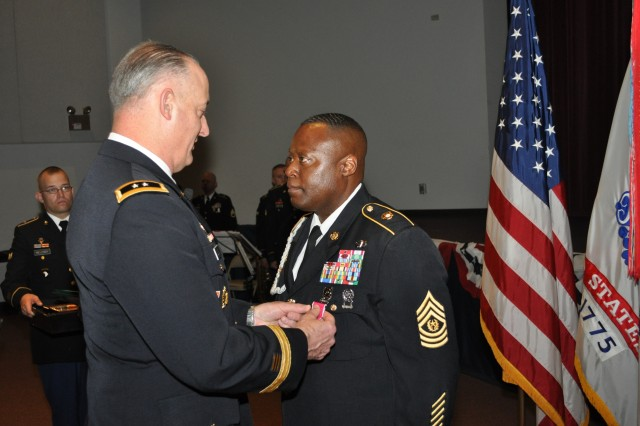 Maj. Gen. Alan R. Lynn, NETCOM commanding general, pins the Legion of Merit on Command Sgt. Major Gerald W. Williams, the former NETCOM command sergeant major, during a retirement ceremony in the Greely Hall auditorium, Aug. 1.  Williams is retiring after 28 years of service in the Army.