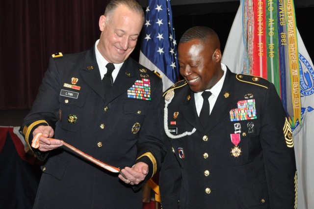 Maj. Gen. Alan R. Lynn, NETCOM commanding general, shows the United States Army Signal Regiment's Silver Order of Mercury award to Command Sgt. Major Gerald W. Williams, the former NETCOM command sergeant major, during a retirement ceremony in the Greely Hall auditorium, Aug. 1.  Williams earned the Silver Order of Mercury for his 28 years of service in the Army and the Signal Corp.