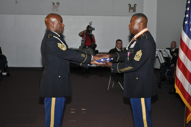 Command Sgt. Major Earl Allen, NETCOM command sergeant major, presents a flag flown at all NETCOM command locations to Command Sgt. Major Gerald W. Williams, the former NETCOM command sergeant major, during a retirement ceremony in the Greely Hall auditorium, Aug. 1.  Williams is retiring after 28 years of service in the Army.