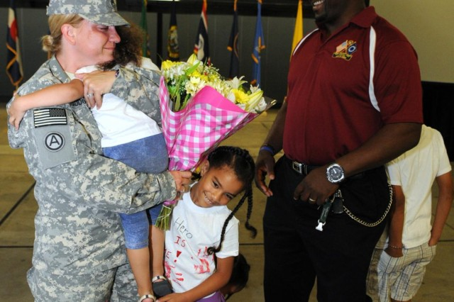 Sgt. 1st Class Michelle Craddock, a senior human resources noncommissioned officer with the 1st Human Resources Sustainment Center and a native of Rockwell City, Iowa, receives greetings from her husband, Benny and children Sophia, Octovianna, Jaylin and Raven, during the 1st HRSC Redeployment at Rhine Ordnance Barracks, Aug. 5.