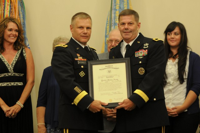 Maj. Gen. Allen W. Batschelet, commanding general of the U.S. Army Recruiting Command, and Brig. Gen. Flem B. Walker Jr., hold a framed copy of the oath of office moments after Batschelet administered the oath to Walker during the ceremony. Walker was promoted to brigadier general Aug. 2 at the Saber and Quill. (U.S. Army photo by Staff Sgt. Candice Funchess)