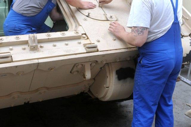 """Richter, right, and Müller, left, both heavy equipment mechanics with Maintenance Activity Kaiserslautern and natives of Kaiserlsautern and Altenkirchen, Germany, respectively, put pieces of an M2A2 Bradley Fighting Vehicle back together at Kaiserslautern Army Depot, July 30, 2013. The 21st Theater Sustainment Command's Theater Logistics Support Center-Europe and Maintenance Activity Kaiserslautern are responsible for retrograding a total of 88 Bradleys."