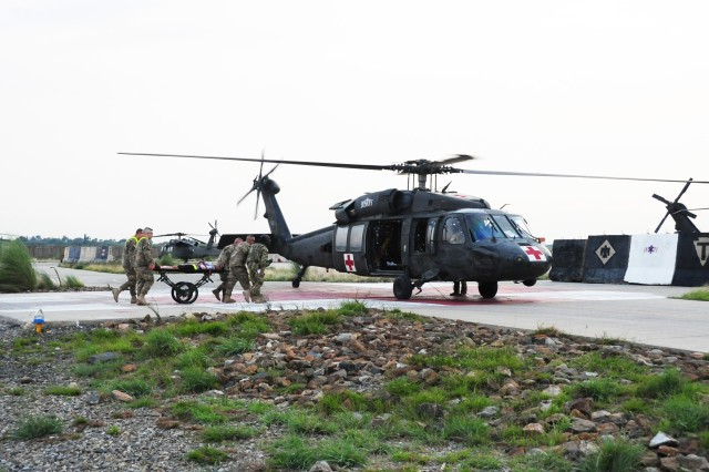 Soldiers from the 801st Brigade Support Battalion transport a simulated casualty to an awaiting HH-60 Black Hawk from Charlie Company, 3rd Battalion, 238th Aviation Regiment, a combined New Hampshire and Michigan National Guard medical evacuation unit, during a mass casualty exercise on Forward Operating Base Salerno, Afghanistan, Aug. 6, 2013.