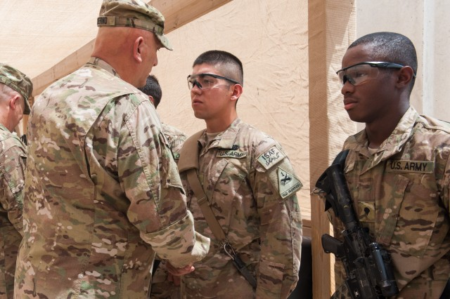 Army Chief of Staff Gen. Raymond T. Odierno presents a Soldier from 1st Brigade, 1st Armored Division, with a Combat Medical Badge, on Forward Operating Base Azizullah, Afghanistan, Aug. 7, 2013. Odierno thanked Soldiers for their dedication to the Army and service to their country during his trip to Afghanistan.