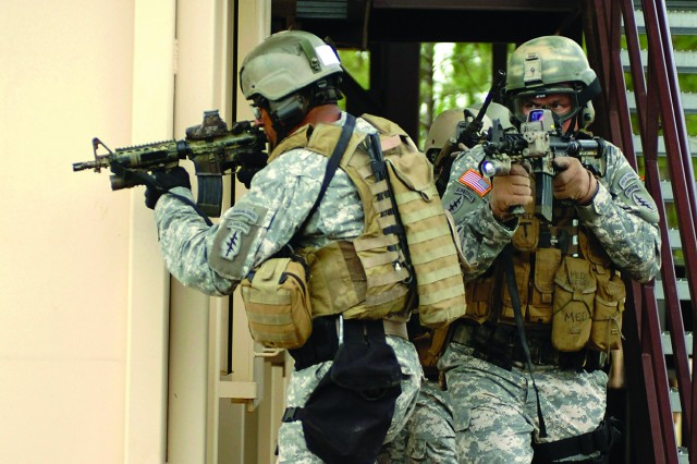 Soldiers with 7th Special Forces Group (Airborne) move alongside a new training facility during urban combat training at Fort Bragg, N.C.