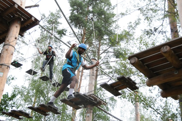 Spc. Robert Walden, a supply clerk with USAG Grafenwoehr's Headquarters and Headquarters Company (below), and Sgt. 1st Class Miguel Martinez, a chaplain assistant with USAG Hohenfels' HHC, make their way through ODR's high ropes course as part of a team-building event, Aug. 8