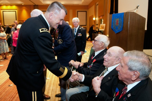 Maj. Gen. Paul E. Funk II, 1st Inf. Div. and Fort Riley commanding general, shakes hands with World War II veteran Al Morfee Aug. 3, 2013, in Jacksonville, Fla., during the 95th annual Society of the 1st Infantry Division Reunion. Seated to the Morfee's right is Harley Reynolds and his left is Charles Shay, both World War II veterans of the 1st Inf. Div.