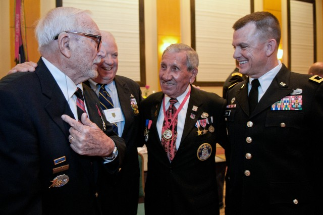 Maj. Gen. Paul E. Funk II, 1st Inf. Div. and Fort Riley commanding general, far right, speaks with World War II veteran Harley Reynolds, former division commander and retired Lt. Gen. Ron Watts and World War II veteran Charles Shay on Aug. 3, 2013, in Jacksonville, Fla., during the 95th annual Society of the 1st Infantry Division Reunion final event, a banquet.
