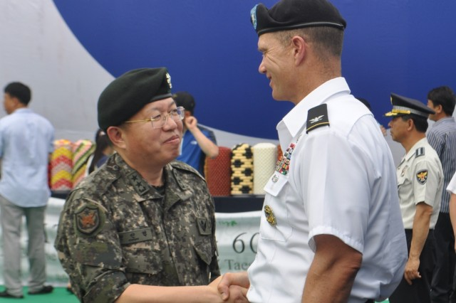 """TAESEONGDONG, South Korea """" Maj. Gen. Chun In-bum, the Senior Member of the United Nations Command Military Armistice Commission, speaks with Col. Michael J. Lawson, commander of 210th Fires Brigade, 2nd Infantry Division, at the Taeseongdong Village 60th Anniversary Celebration in the Joint Security Area of the Demilitarized Zone, South Korea August 2, 2013. The village is a symbol of the success of the ROK-U.S. Alliance that was forged during the Korean War and has grown stronger over the last 60 years. (U.S. Army photo by Capt. Kelly E. McKenzie, 210th Fires Brigade Public Affairs Officer/Released)."""