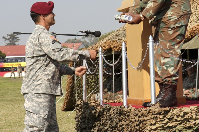 1st Lt. William Israel, Charlie Company, 1st Battalion, 325th Airborne Infantry Regiment, from Fort Bragg, N.C., hands the ceremonial scroll to South African Maj. Gen. Ephraim Phako, deputy chief of Joint Operations, during the closing ceremony of Shared Accord 13, at Port Elizabeth, South Africa, Aug. 5, 2013. Shared Accord is a biennial training exercise which promotes regional relationships, increases capacity, trains U.S. and South African forces, and furthers cross-training and interoperability.