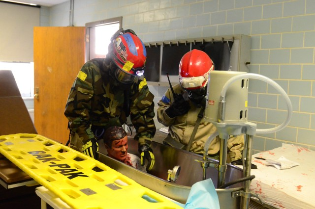 MUSCATATUCK URBAN TRAINING CENTER, Ind. - Two Soldiers from the 300th Chemical Company, Morgantown, W.Va., evaluate a patient located in a bath tube, inside of the hospital, while participating in a simulated hospital evacuation scenario during the U.S. Army North (Fifth Army) lead Vibrant Response 13-2 training exercise, Aug. 5, Muscatatuck Urban Training Center, Muscatatuck, Ind.  All of the patients were evacuated from the hospital and taken across the street to a mobile decontamination site to be decontaminated prior to receiving a medical evaluation by a medical support team. (Army Photo by Staff Sgt. Alexandria Brimage-Gray, 27th Public Affairs Detachment)