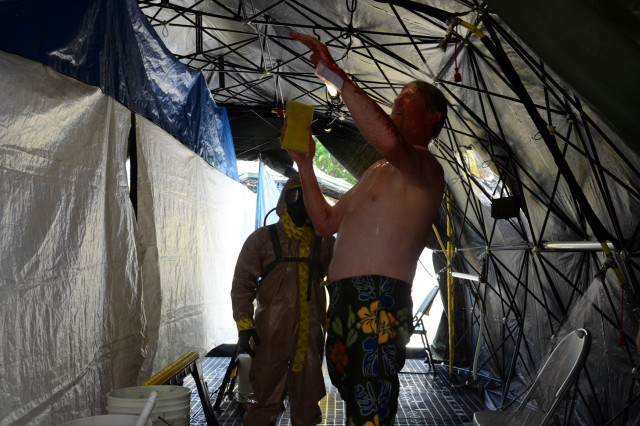 MUSCATATUCK URBAN TRAINING CENTER, Ind. - A Soldier from the 377th Chemical Company, Richmond, Va., observes an ambulatory displaced hospital patient shower in the mobile decontamination site while participating in a simulated hospital evacuation scenario during the U.S. Army North (Fifth Army) lead Vibrant Response 13-2 training exercise, Aug. 5, Muscatatuck Urban Training Center, Muscatatuck, Ind.  All of the patients were evacuated from the hospital and taken across the street to a mobile decontamination site to be decontaminated prior to receiving a medical evaluation by a medical support team. (Army Photo by Staff Sgt. Alexandria Brimage-Gray, 27th Public Affairs Detachment)
