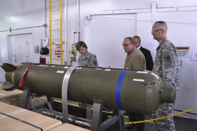 Brig. Gen. Kristin K. French (left), commander of the Joint Munitions and Lethality Life Cycle Management Command and Joint Munitions Command, examines the Sensor Fuzed Weapon produced at McAlester Army Ammunition Plant as David Higgins, MCAAP site leader for Textron Defense Systems, explains its operation.  The SFW is produced by MCAAP under a contract with Textron Defense Systems. Col. Joseph G. Dalessio, MCAAP commander, is on the right. The visit was the general's first to the MCAAP. She assumed command of MCAAP's higher headquarters July 2, 2013. (U.S. Army photo by Lea Giaudrone)