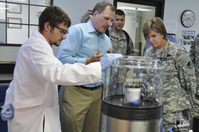 Bradley Black (center), director of Quality Assurance, explains the demonstration of a new mixer technology to Brig. Gen. Kristin K. French (right), commander of the Joint Munitions and Lethality Life Cycle Management Command and Joint Munitions Command, during her initial visit to McAlester Army Ammunition Plant July 30, 2013. The new Resonant Acoustic Mixing enables MCAAP to mix plastic explosives safer, more efficiently and without process waste. MCAAP chemist, Treavor Price (left) and 1st Lt. Chris Ciman (rear), also watch the process. The general assumed the position of commander of MCAAP's higher headquarters July 2, 2013. (U.S. Army photo by Lea Giaudrone)