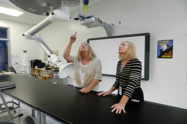 Ronda Frueauff (left), Ph.D., former Fort Huachuca Accommodation Schools superintendent, and Bonnie Austin, current Fort Huachuca Accommodation Schools superintendent, describe the exhaust systems like the one pictured inside the eighth grade Science, Technology, Engineering and Math Lab at Colonel Smith Middle School at Fort Huachuca, Ariz. Much like the moveable science stations found in the lab this overhead unit also supports flexibility.