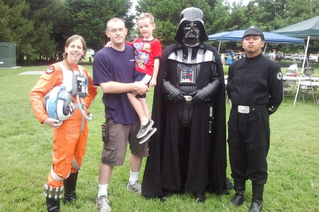 Darth Vader, an Imperial Crewman, and a Rebel Pilot pose for a picture with Corporal Matthew T. Morgan and his son during the annual JFHQ-NCR/MDW Organizational Day picnic at Fort Lesley J. McNair, August 7.