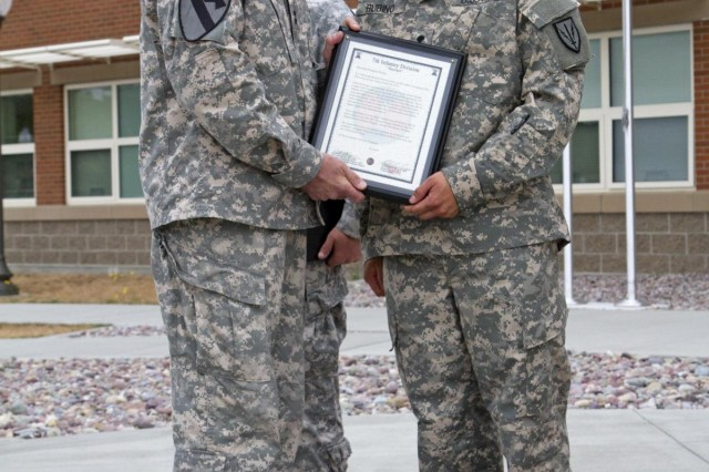 Maj. Gen. Stephen R. Lanza (left), commanding general of the 7th Infantry Division, presents Spc. Benjamin Rubino, 201st Brigade Special Troops Battalion, 201st Battlefield Surveillance Brigade, with a Bayonet Soldier of the Month plaque, Aug. 2, outside of the division headquarters, for his actions June 29, 2013. On that day, Rubino, of Olympia, Wash., received a photo on his cell phone of his former squad leader holding a loaded gun to his head. He quickly alerted the authorities at Schofield Barracks, Hawaii, where the squad leader was located, and they were able to get the soldier to the hospital for treatment and observation.