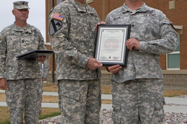 """Maj. Gen. Stephen R. Lanza (center), 7th Infantry Division commanding general, presents Sgt. Larry Blais with a Bayonet Soldier of the Month certificate and commanders coin Aug. 2, while Command Sgt. Maj. Delbert Byers, the division's command sergeant major, looks on. Blais was recognized for his actions on May 5, 2013. Blais, a noncommissioned officer with the 5th Battalion, 20th Infantry Regiment, 3rd Stryker Brigade Combat Team, 2nd Infantry Division, was performing a barracks inspection with his soldiers when he noticed a soldier who was severely intoxicated. After assessing the situation, the Lewiston, Maine, native rushed the soldier to the hospital for immediate medical attention. Blais said he was """"just doing what a leader should be"""" doing, by performing barracks inspections, and said soldiers should continue to check on and take care of one another."""