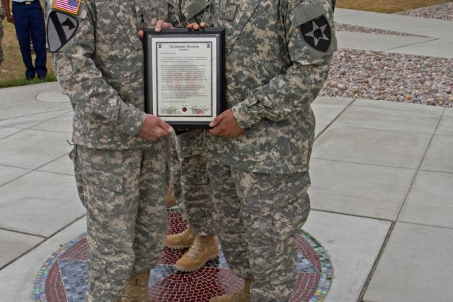 "Douglas, Ariz., native Pvt. Marvin Frisby (right) poses with Maj. Gen. Stephen R. Lanza, commanding general of the 7th Infantry Division, outside the division headquarters, Joint Base Lewis-McChord, Wash., Aug. 2, after Lanza presented him with a Bayonet Soldier of the Month certificate and commander's coin for his actions March, 27, 2013. Frisby, with the 2nd Brigade Support Battalion, 2nd Stryker Brigade Combat Team, 2nd Infantry Division, was on gate guard duty at the Madigan Gate entrance to JBLM, when a women in labor was driving through. Realizing that there was not enough time to get her to Madigan Army Medical Center, Frisby helped the woman to deliver the baby at the gate. However, Frisby soon realized the umbilical cord was wrapped around the baby's neck; he immediately repositioned the child in order to allow the baby to breathe. ""This is a great exmaple of a Soldier who was able to remain calm, despite the pressure of the situation, and do what he needed to do to ensure the safety of the baby and mother,"" Lanza said. ""He helped give life, and for that we [7th Infantry Division leadership] are extremely proud."""