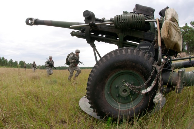 Paratroopers from the 82nd Airborne Division's 1st Brigade Combat Team run to their M119A3 105mm all-digital howitzer after it was transported by a CH-47 Chinook helicopter, Aug. 7, on Fort Bragg, N.C. The Gun Devils, who are part of the first unit in the Army to field the all-digital howitzers, sling-loaded their howitzers for an air assault gun raid training mission undertaken as part of the new equipment fielding process. (U.S. Army photo by Staff Sgt. Mary S. Katzenberger)