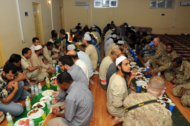 Soldiers and civilians enjoy an iftar at the Kandahar Islamic Center on Kandahar Airfield, Afghanistan, during Ramadan July 21, 2013. An iftar is a breaking of the fast meal. The Muslims gathered together to eat and pray after a day of fasting in observance of Ramadan. (U.S. Army photo by Staff Sgt. Mark Albright)