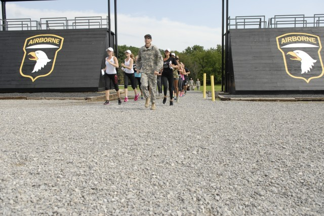 FORT CAMPBELL, Ky. - Sgt. 1st Class William McBride, an instructor at the Sabalauski Air Assault School leads Fox Sports Girls on a run from the obstacle course to the rappel tower here Aug. 12. The Fox Girls, along with current and former professional athletes, were at Fort Campbell as part of a community relations program to promote the launch of its new Fox Sports 1 channel.
