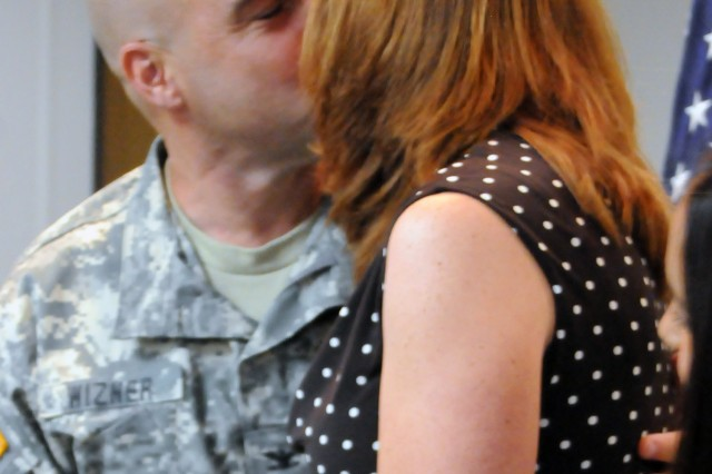 Central Technical Support Facility Director, Col. Anthony Wizner, gets a congratulatory kiss from wife Jennifer at the conclusion of his Aug. 12 promotion ceremony.